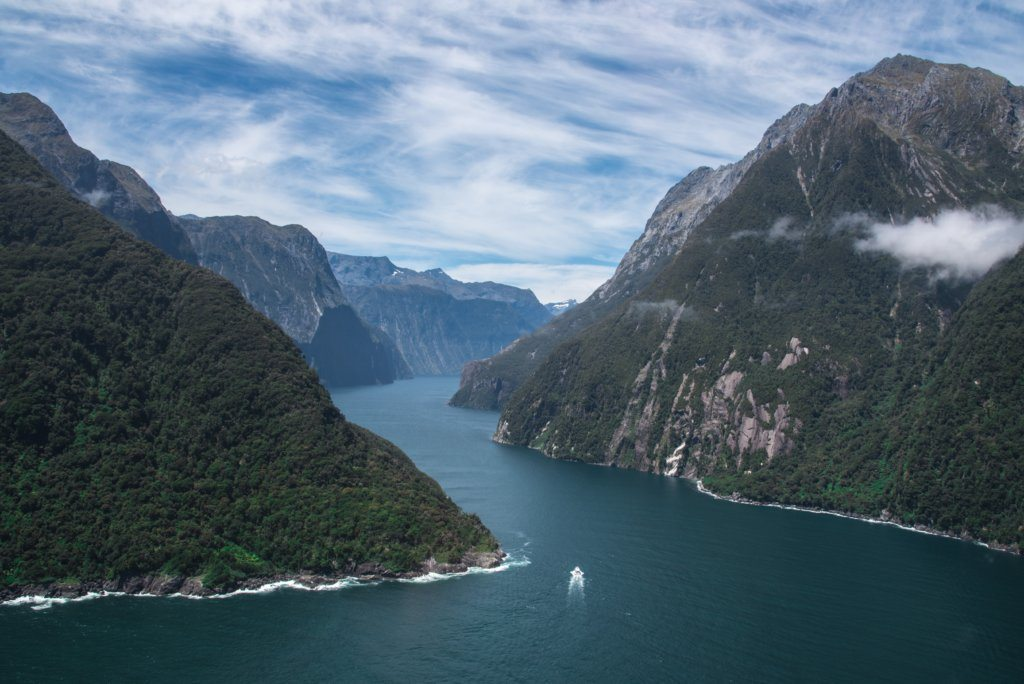 An aerial view of the Milford Sound weaving between two mountainous peaks