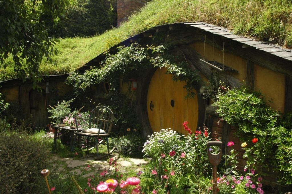 Yellow hobbit house with a chair out the front covered in flowers and foliage