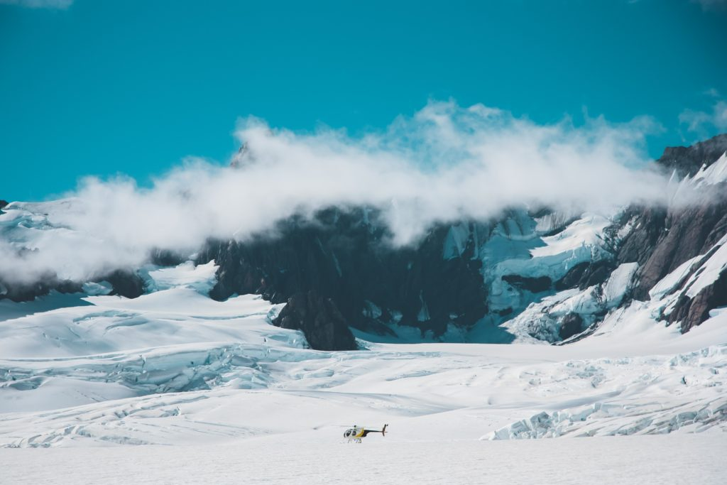 a long distance photograph of a small helicopter sat on a glacier with blue skies above and a line of fluffy white clouds